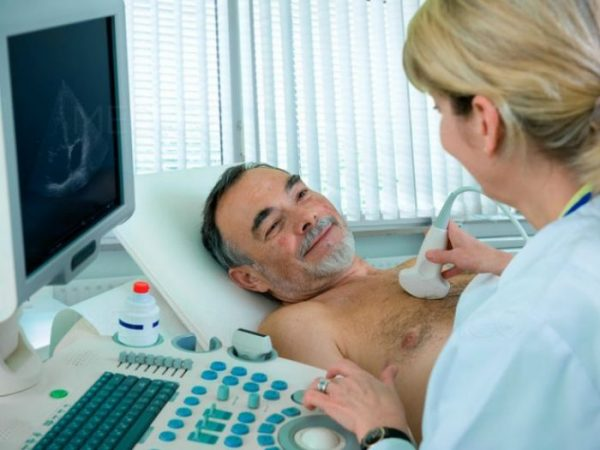 An ultrasound device is applied to the chest, delivering sound waves that a computer detects and displays as images.